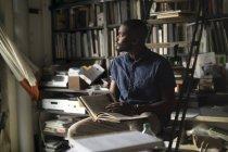 Giovane uomo con il libro nel suo studio — Foto stock
