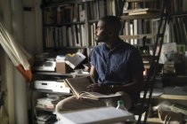 Молода людина з книги у своїй студії — стокове фото