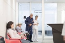 Nurse supporting patient in waiting area — Stock Photo