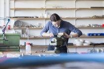 Junge Frau mit Schutzbrille arbeitet mit Feile — Stockfoto
