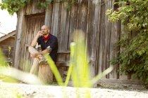 Портрет задумчивого мужчины, сидящего перед деревянной хижиной — стоковое фото