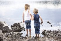 Boy and girl standing hand in hand at lakeshore — Stock Photo