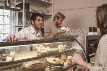 Junge Frau wählt Kuchen aus Kuchentheke im Café — Stockfoto