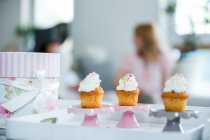 Three cup cakes on tray, people in background at home — Stock Photo