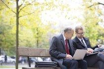Hommes d'affaires avec ordinateur portable assis sur un banc de parc — Photo de stock