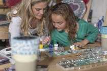 Mother and daughter doing crafts in home garage — Stock Photo