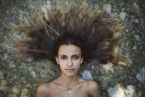 Портрет женщины, лежащей на камне с взъерошенными волосами — стоковое фото