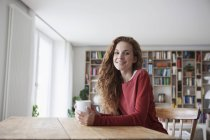 Frau sitzt am Tisch aus Holz mit Tasse — Stockfoto