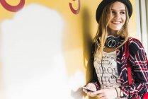 Улыбается девочка-подросток, прислонившись к стене — стоковое фото