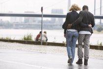 Jeune couple se promener au bord de la rivière — Photo de stock