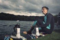 Розслабленої молодих wakeboarder сидячи в озера — стокове фото