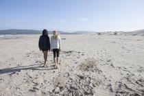 Vista posterior de dos mujeres caminando por la playa - foto de stock