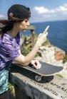 Espanha, Gijon, mulher skatista ler mensagem de texto — Fotografia de Stock