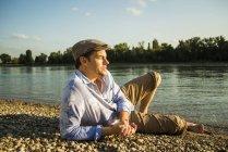 Mann mit Mütze Entspannung am Flussufer in der Abenddämmerung — Stockfoto