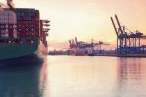 Germany, Hamburg, freight ships at city harbor at sunset — Stock Photo