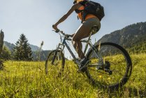 Austria, Tyrol, Tannheim Valley, young woman on mountain bike in alpine landscape — Stock Photo