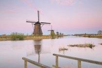Нидерланды, Киндердейк, Киндердейк ветряные мельницы в сумерках против воды — стоковое фото