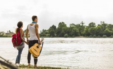 Young couple standing by the riverside with guitar — Stock Photo