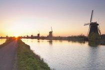 Netherlands, Kinderdijk, Kinderdijk wind mills at twilight over water — Fotografia de Stock