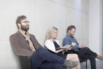 Люди сидять у зал очікування в офісі — стокове фото