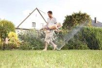 Батько і його маленький син весело разом в саду — стокове фото
