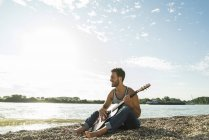 Young man with guitar sitting by the riverside — Stock Photo
