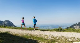 Austria, Tyrol, Tannheim Valley, young couple jogging in mountains — Stock Photo