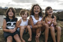 Spanien, Gijon, Gruppenbild von vier kleinen Kindern sitzen an der felsigen Küste, die Spaß — Stockfoto