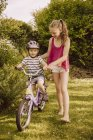 Girl helping little boy riding bicycle in garden — Stock Photo