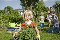 Girl carrying tray with seedlings in garden with family on background — Stock Photo