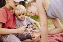 Three children on blanket looking through a magnifying glass — Stock Photo
