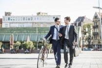 Due uomini d'affari con bici e smart phone a piedi in città — Foto stock