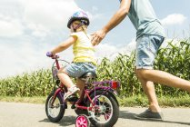 Father accompanying daughter on bike — Stock Photo