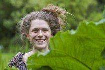 Портрет улыбающейся молодой женщины с булочкой за листом — стоковое фото