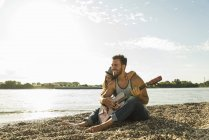 Happy young couple with guitar by the riverside — Stock Photo