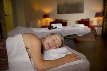 Haute femme couchée sur la table de massage avec des yeux fermés — Photo de stock