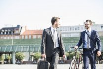 Two young businessmen walking in city, pushing bicycle — Stock Photo