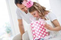 Chica con corona rosa sosteniendo bolsas de regalo, padre mirando en casa - foto de stock
