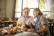 Smiling senior couple with digital tablet having breakfast in a cafe — Stock Photo