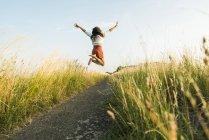 Enthousiaste jeune femme sautant sur le chemin d'accès dans le champ — Photo de stock