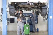 Dois mecânicos de carro no trabalho na garagem de reparação — Fotografia de Stock