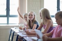 Schoolgirl in classroom with girls raising hand — Stock Photo