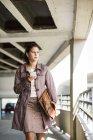 Junge Frau mit Smartphone im Parkhaus — Stockfoto