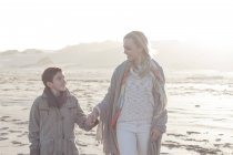 Mother and her son walking on the beach at beautiful nature — Stock Photo