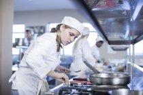 Девочка-подросток готовит на кухне — стоковое фото