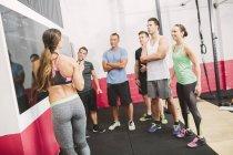 Crossfit trainer explicando exercícios no quadro negro — Fotografia de Stock