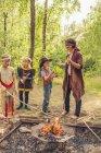 Alemanha, Saxônia, índios e cowboy festa, marshmallows de rasting crianças em varas — Fotografia de Stock
