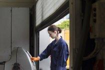 Jovem mulher que trabalha na garagem de reparação — Fotografia de Stock