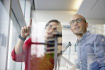 Man and woman in office discussing behind glass pane — Stock Photo