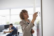 Young man in office writing on whiteboard — Stock Photo